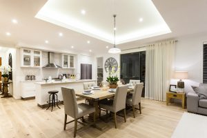 Modern living room and kitchen with a wooden floor illuminated at night with lights
